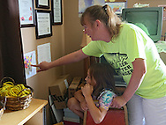 Raegan Junge (from left), 8, looks at a map as her mother, Crystal Junge, both of Keystone, points to the various states they have helped at her house in Keystone on Wednesday, July 17, 2013.