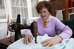 Grandmother using a sewing machine at home,