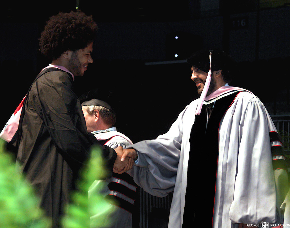 Juan Luis Guerra felicita a unos de los graduandos durante la reciente.graducian en la Universidad de Berklee, Mayo 2009. En el mismo acto,Guerra.fue envestido con titulo honorifico de Doctor, por sus trunfos e influencia en la musica internacional..
