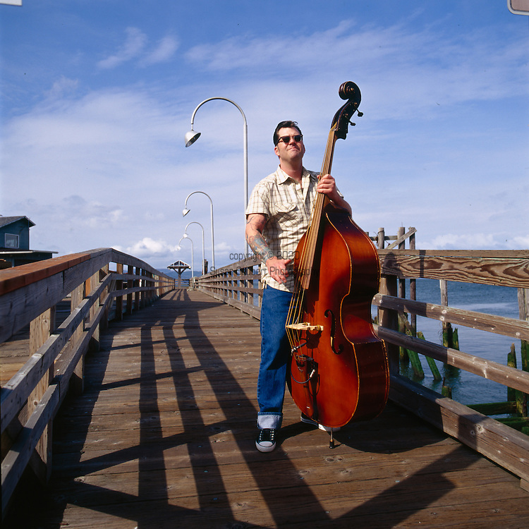 Musician Josh Baer practices his stand-up bass on one of the public boardwalks in downtown Astoria, Oregon