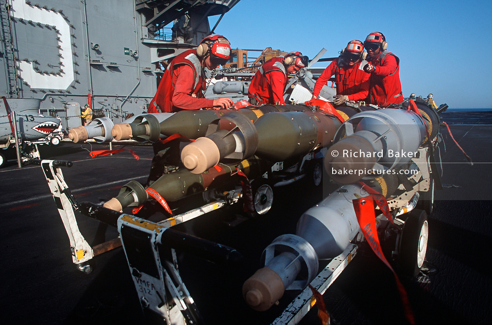 Red-shirted US Navy ordnance crewmen prepare to fit smart bombs and missiles to an F/A-18 fighter jet on the deck of US Navy aircraft carrier USS Harry S Truman during its deployment patrol of the no-fly zone at an unknown location in the Persian Gulf, on 8th May 2000, in the Persian Gulf. The Truman is the largest and newest of the US Navy's fleet of new generation carriers, a 97,000 ton floating city with a crew of 5,137, 650 are women. (Photo by Richard Baker / In Pictures via Getty Images)