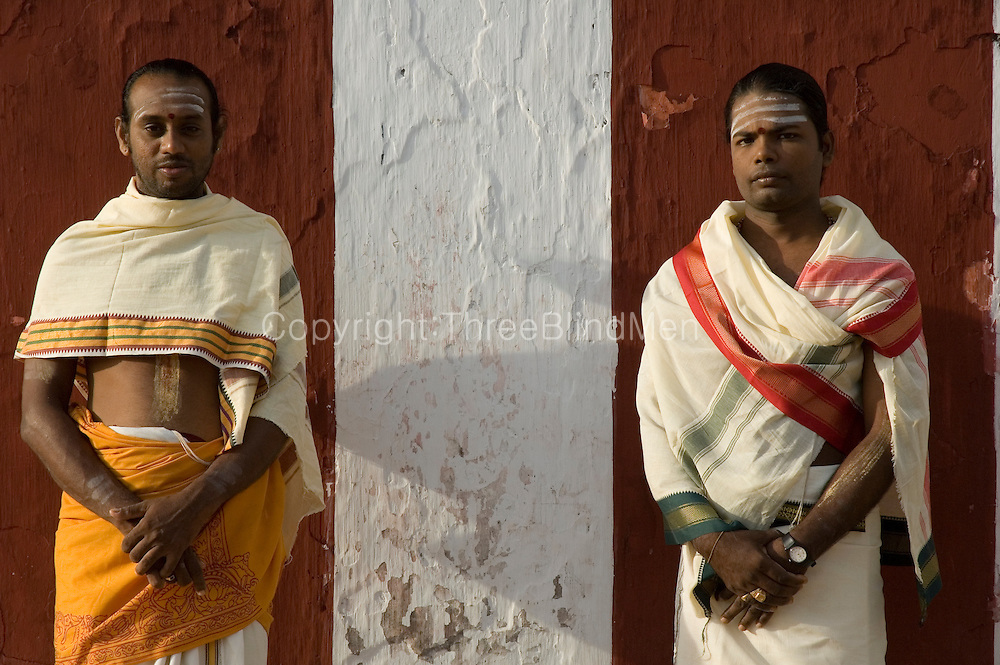 Brahmin Priests stand beside the red and white wall of the Nallur Kandaswamy Temple. Jaffna.