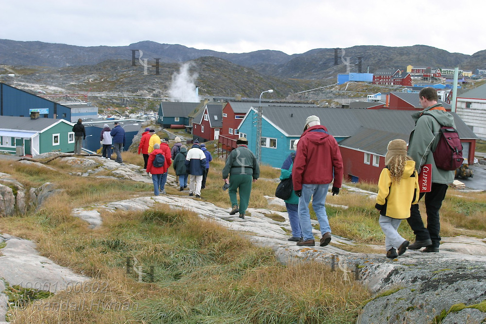 Tourists walk down rocky hill toward colorfully painted homes and buildings of Ilulissat, third largest town in Greenland.
