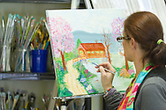 Campbell Hall, New York - A woman works on her painting at The Art Cottage on April 9, 2014.