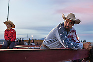 Kris Ratzlaff, a volunteer for the Pro-West Rodeo Finals, and his son Jacob, left, look on at saddle bronc riders as the sun goes down on the Kootenai County Fairgrounds Saturday October, 5.