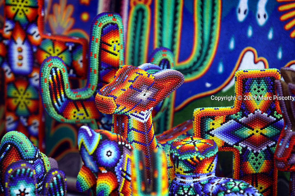 "SHOT 2/12/09 8:34:41 AM - Huichol beaded artwork for sale on the main square in Sayulita, Mexico. The beaded art is a relatively new innovation and is constructed using glass, plastic or metal beads pressed onto a wooden form covered in beeswax. Common bead art forms include masks, bowls and figurines. Like all Huichol art, the bead work depicts the prominent patterns and symbols featured in the Huichol religion. The Huichol or Wixáritari are an indigenous ethnic group of western central Mexico, living in the Sierra Madre Occidental range in the Mexican states of Nayarit, Jalisco, Zacatecas, and Durango. Sayulita is a small fishing village about 25 miles north of downtown Puerto Vallarta in the state of Nayarit, Mexico. Known for its consistent river mouth surf break, roving surfers ""discovered"" Sayulita in the late 60's with the construction of Mexican Highway 200. Today, Sayulita is a prosperous growing village of approximately 4,000 residents. Hailed as a popular off-the-beaten-path travel destination, Sayulita offers a variety of activities such as horseback riding, hiking, jungle canopy tours, snorkeling and fishing. Still a mecca for beginner surfers of all ages, the quaint town attracts upscale tourists with its numerous art galleries and restaurants as well. Sayulita has a curious eclectic quality, frequented by native Cora and Huichol peoples, travelling craftsmen as well as international tourists. Sayulita is the crown jewel in the newly designated ""Riviera Nayarit"", the coastal corridor from Litibu to San Blas. It's stunning natural beauty and easy access to Puerto Vallarta have made Sayulita real estate some of the most sought after in all of Mexico..(Photo by Marc Piscotty / © 2009)"