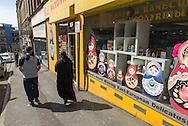 A Muslim couple passes a shop selling East European products. / Couple musulman passe devant un mini supermarché qui vend des produits d'alimentation d'Europe de l'Est, Bradford.