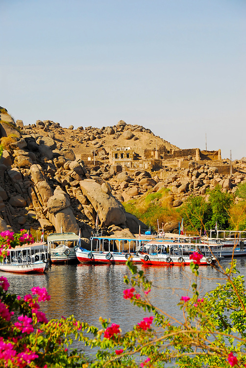 Tourist boats wait in the water opposite the Temple of Philae in Aswan, Egypt.