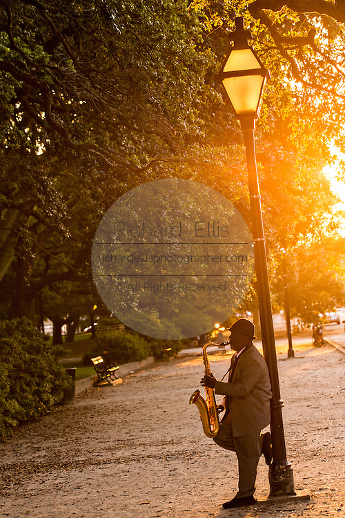 A street musician plays the saxophone along White Point Gardens on the battery in the historic district during sunset August 11, 2013 in Charleston, SC.