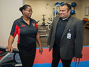 Hartman Middle School principal Geovanny Ponce, right, talks with instructtor Yonsuetta Johnson, left, in the new workout room during the dedication of the school's Health and Medical wing, April 3, 2014.