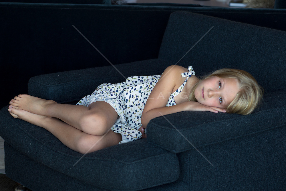 little girl resting on a chair