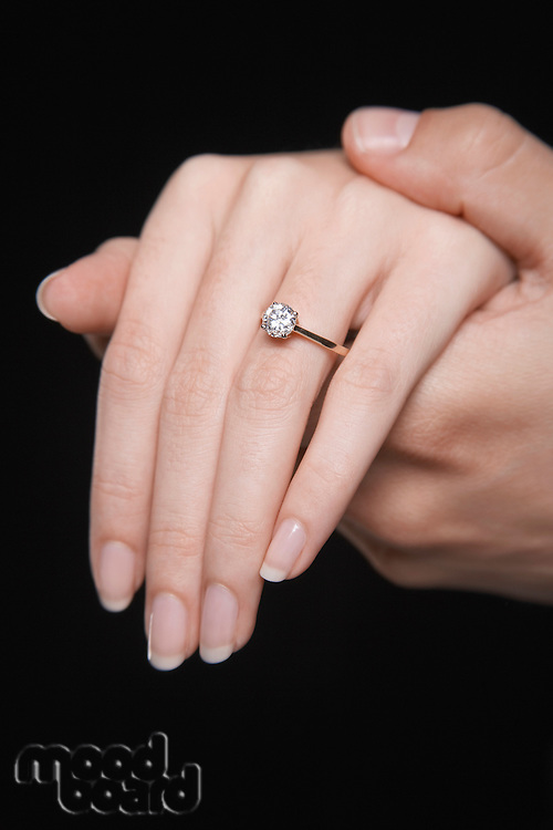 Man holding woman's hand displaying engagement ring close up of hand