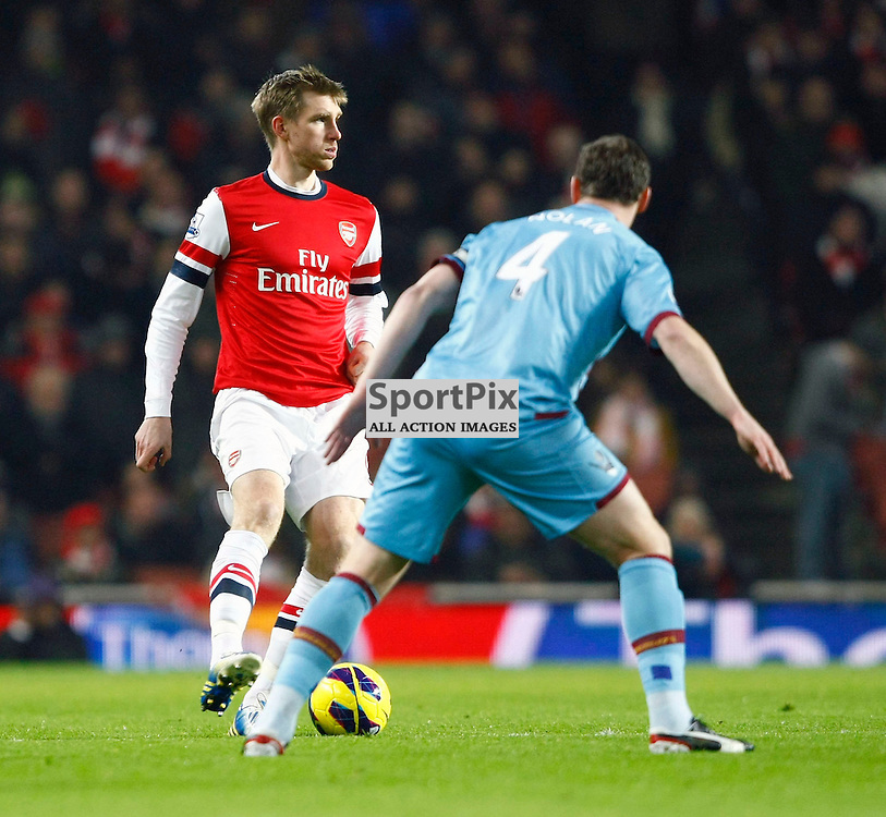 Alan Ramsey looks for an out ball whilewatched by West Ham's Kevin Nolan. Arsenal v West Ham United Premiership 23 January 2013