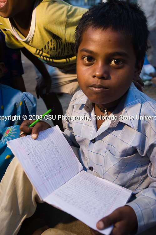 A boy looks up from his studies in a tent community in Bangalore, India.