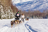Musher Mark Hartum is followed by Bill Kornmuller and Lina Streeper in the Fur Rendezvous World Sled Dog Championships at Campbell Airstrip in Anchorage in Southcentral Alaska. Winter. Afternoon.