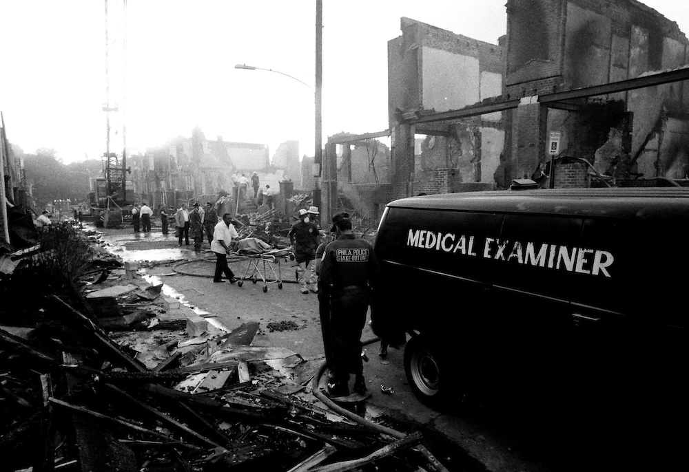 Philadelphia Police and members of the Medical Examiners remove bodies from the MOVE house on Osage Ave. Eleven MOVE members died after an all day police assault went awry which resulted in an entire block of homes burning to the ground. May 13th, 1985.© Ed Hille / The Philadelphia Inquirer.