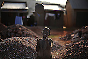 12-03-21   -- KAMPALA, UGANDA -- Josephine Amala, 6, plays amidst piles of aggregate in the Acholi Quarter on March 21, 2012. Since the early 1990's, people from the Acholi tribe (and from other northern tribes) migrated to a plot of land in a suburb of Kampala to escape the violence in the north. Now, rather than returning to their ancestral lands, some are calling the Acholi Quarter home. Many residents, unable to find well-paying employment, make a living mining and crushing rocks by hand.. Photo by Daniel Hayduk