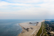 Nederland, Zuid-Holland, Gemeente Westland,  28-09-2014; Delflandse Kust ter hoogte van Ter Heijde en Monster, Den Haag aan de horizon. De Zandmotor is een kunstmatig schiereiland ontstaan door het opspuiten van zand voor de kust. Wind, golven en stroming zullen het zand langs de kust verspreiden waardoor breder stranden en duinen ontstaan. De zandmotor is een experiment in het kader van kustonderhoud en kustverdediging. <br /> Sand Engine, artificial peninsula build by the raising of sand for the coast of Ter Heijde (near the Hague, at the horizon). Wind, waves and currents will distribute the sand along the coast yielding wider beaches and dunes along the coastline. The Sand Engine is a experiment for coastal maintenance of coastal defense.<br /> luchtfoto (toeslag op standard tarieven);<br /> aerial photo (additional fee required);<br /> copyright foto/photo Siebe Swart