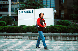 CHINA SHANGHAI NOV01 - Chinese woman walks past Siemens sign in Pudong, residence to many foreign companies' headquarters.. . . jre/Photo by Jiri Rezac. . © Jiri Rezac 2001. . Contact: +44 (0) 7050 110 417. Mobile:  +44 (0) 7801 337 683. Office:  +44 (0) 20 8968 9635. . Email:   jiri@jirirezac.com. Web:     www.jirirezac.com