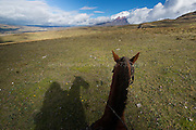 Horseback riding in Ecuador's high altitude grasslands near Cotopaxi volcano.