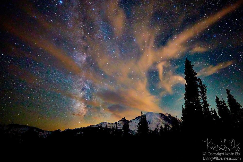 A band of clouds stretches from the summit of Mount Rainier across the Milky Way after midnight in this view from near Sunrise in Mount Rainier National Park, Washington. Mount Rainier, which has a summit of 14,411 feet (4,392 meters), is the highest mountain in Washington state and largest volcano in the Cascade Range.