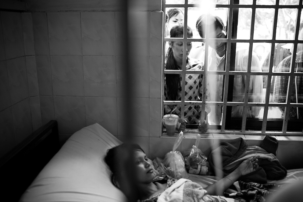 A woman injured in the stampede is visited by her friends at Calmette Hospital in Phnom Penh, Cambodia, where many of the fatalties were also brought. Several hundred perished in a stampede tragedy when an unknown event sparked panic and thousands attempted to flee Diamond Island in the middle of the Mekong River over the bridge connecting it to the river bank.