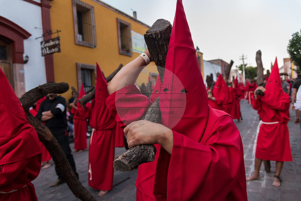 Hooded penitents carry wooden crosses during the Procession of Silence through the streets on Good Friday during Holy Week March 30, 2018 in Querétaro, Mexico. The penitents, known as Nazarenes, carry the heavy crosses and drag chains in a four hour march in memory of the passion of Christ.