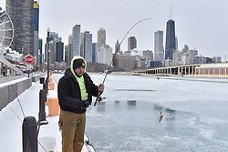© Licensed to London News Pictures. 31/12/2017. CHICAGO, USA.  A man takes part in ice fishing off Navy Pier. The waters of Lake Michigan around Chicago have frozen during a period of sub-zero temperatures.  Extremely cold conditions are forecast to continue into the New Year. Photo credit: Stephen Chung/LNP