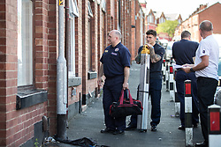 © Licensed to London News Pictures . 08/07/2017 . Bolton , UK . Firefighters offer householders free smoke detectors in houses adjacent to the scene on Rosamond Street in Daubhill , where a fatal house fire burned through a mid-terrace house this morning (Saturday 8th July 2017) . Firefighters responded at 9am this morning (Saturday 8th July 2017) . A family of five are reported to have been inside at the time and there are understand to me multiple fatalities . Photo credit : Joel Goodman/LNP