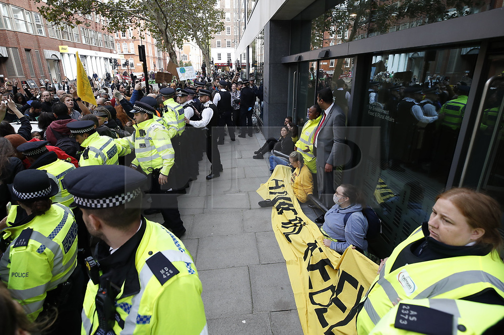 © Licensed to London News Pictures. 09/10/2019. London, UK. Extinction Rebellion activists have locked themselves to the front doors of the Department for Environment during a third day of protests in central London. The climate change group intend to blockade the Westminster area for two weeks to demand that the government takes immediate and decisive action on climate change. Photo credit: Peter Macdiarmid/LNP