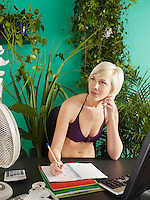 Female office worker wearing bikini behind desk