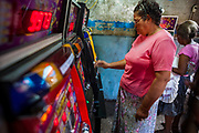 """08 JANUARY 2007 - MANAGUA, NICARAGUA:  A woman plays the slot machines in a """"casino"""" in Mercado Oriental, the main market that serves Managua, Nicaragua. The market encompasses dozens of square blocks and is the largest market in Central America. The government of Violetta Chamorro legalized gambling in 1990. There are casinos in most of the tourist hotels and dozens of small """"mom and pop"""" slot machine casinos in the market. Photo by Jack Kurtz"""