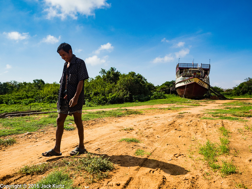 31 MAY 2016 - SIEM REAP, CAMBODIA: The foreman of the repair crew working the Tara walks to a small shop in a village near the beached boat. The Tara is a river freighter and passenger boat assembled in Vietnam, then a French colony, in 1927. Most recently it's used to take tourists on dinner cruises on the Tonle Sap Lake. Because of the drought in Cambodia, the Tara is beached and unable to navigate the nearly empty canals that lead to the Tonle Sap Lake. The boat's owners are repairing and refurbishing it while it's beached and hope that the coming rainy season will flood the canal enough to let the Tara get back to the lake.     PHOTO BY JACK KURTZ