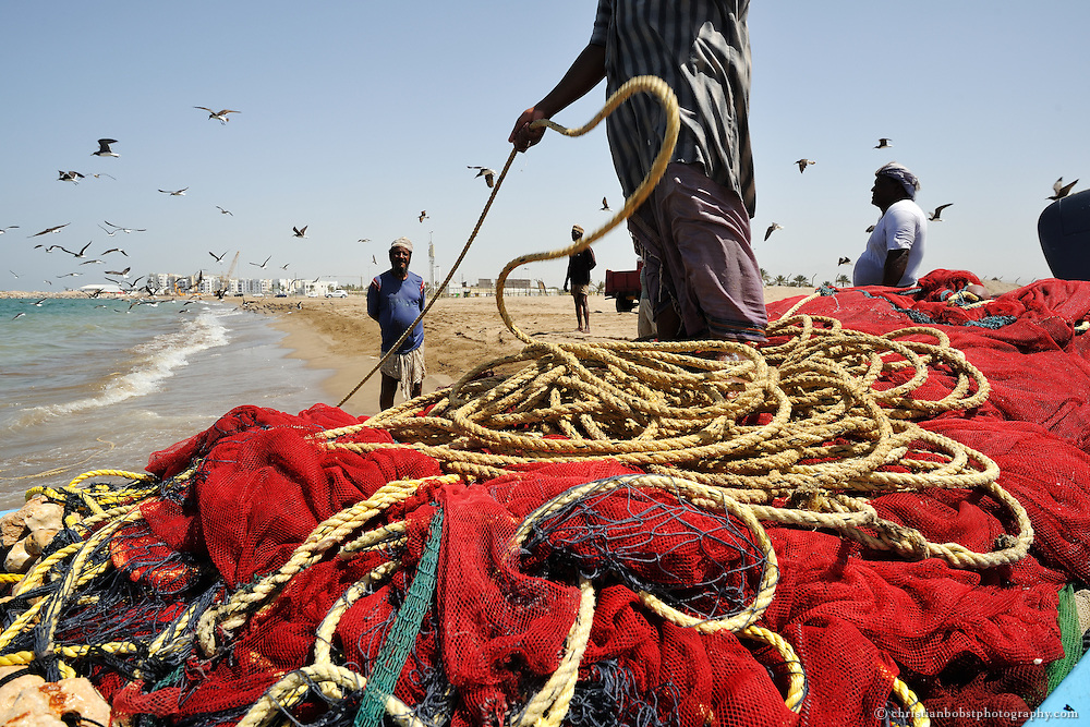 Fishermen at the wave beach in Muskat, Oman