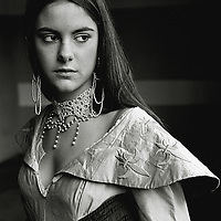 A young woman wearing an ornate necklace and silk clothing