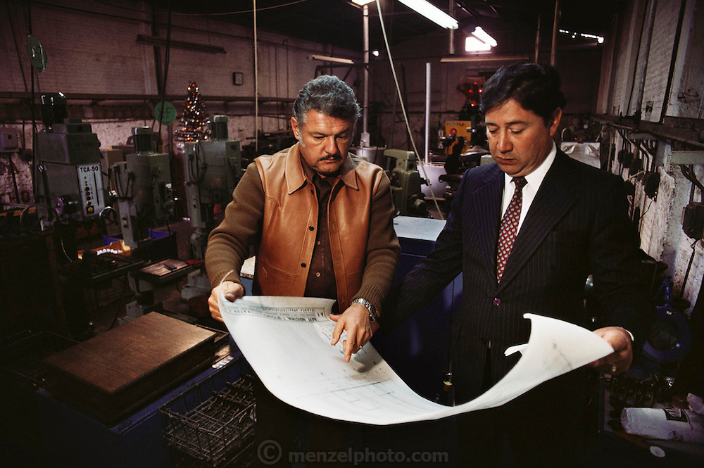 Sr. Amifua and Sr. Carona consult plans at an autoparts factory. Queretaro, Mexico.