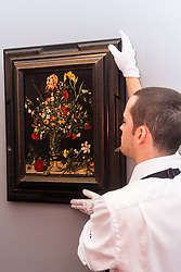 "Sotheby's London, November 28th 2014.Sotheby's hold a preview for their December 3rd sale of Old Master and British Paintings at their Bond Street gallery. The exhibition runs from November 29th to December 3rd. PICTURED: A Sotheby's gallery tedchnician hangs Ambrosius Bosschaert the Elder's ""Still life of flowers including irises, lillies, narcissi, lilly-of-the-valley and carnations in a tall glass vase, set on a stone ledge"", which was painted in 1606. It has an estimated value of up to £900,000 at auction."