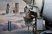 Cement mixer lorry and a property developer's billboard showing a large aerial image of London skyscrapers in low cloud.