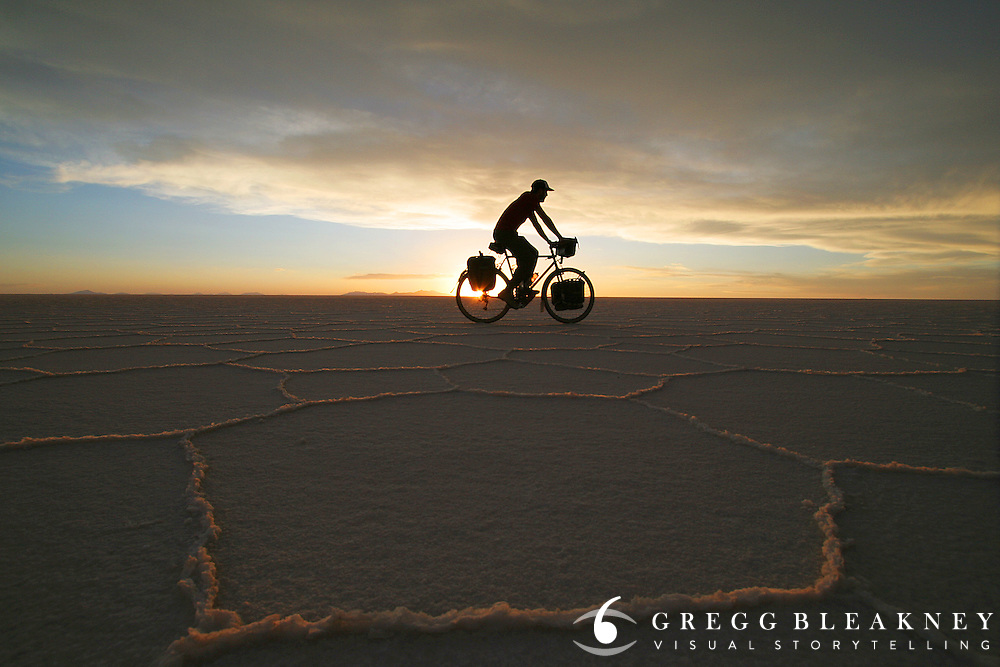 Brook Allen cycles over the Salar de Uyuni at Sunset - Bolivia - South America