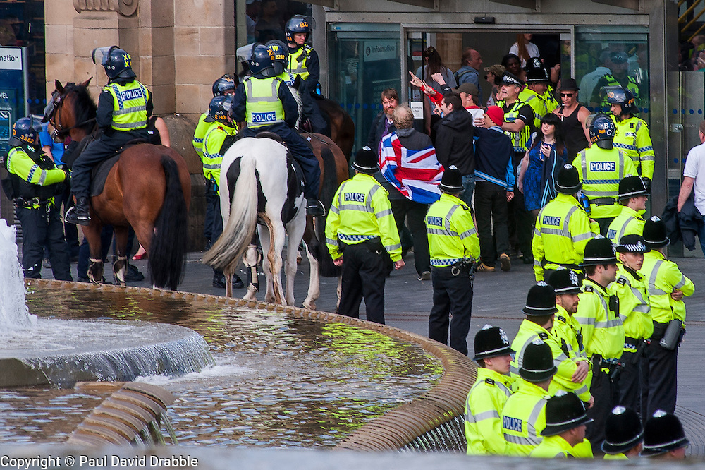The English Defence League (EDL) return to Sheffield to lay flowers at Sheffield War Memorial . resulting in a police operationlasting over 5 hours involving Officers from Wales, South Yorkshire, Greater Manchester, West Yorkshire, Lancashire and Mersyside Police forces.  The EDL say goodbye to Sheffield as they are escorted in smaller groups in the Railway Station.<br /> <br /> <br /> 8 June 2013<br /> Image © Paul David Drabble<br /> www.pauldaviddrabble.co.uk