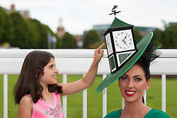 Repro Free: 08/08/2013 Juliana Pratofiorito from New York checks the time of the winner of the 'Most Creative Hat' at the Blossom Hill Ladies' Day at the Dublin Horse Show created and worn by Suzanne O'Brien. Picture Andres Poveda