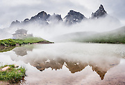 At Refugio Baita Segantini, fog swirls around the Pala group (Pale di San Martino) and reflects in a pond. The sharp pyramid of Cimon della Pala (or Cimone, 3184 m/10,446 ft) is known as the Matterhorn of the Dolomites (il Cervino delle Dolomiti). To its left is Cima della Vezana (3192m), highest of the Pala Dolomites. Walk from Passo Rolle to Baita Segantini near the mountain resort of San Martino di Castrozza, in Trentino-Alto Adige/Südtirol region of Italy, Europe. 200 million years ago, Triassic coral reefs fossilized into Dolomite. Collision of tectonic plates lifted the Dolomites within the Southern Limestone Alps. UNESCO honored the Dolomites as a natural World Heritage Site in 2009. This panorama was stitched from 6 overlapping photos.