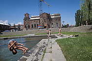 Children swimming in the city fountain by the Church of the Holy Saviour of All ...Church is resembling Mother Cathedral in Ani . Construction of the church began in 1859 and was completed in 1873. It was greatly damaged by the 1988 Spitak earthquake and is currently being reconstructed..