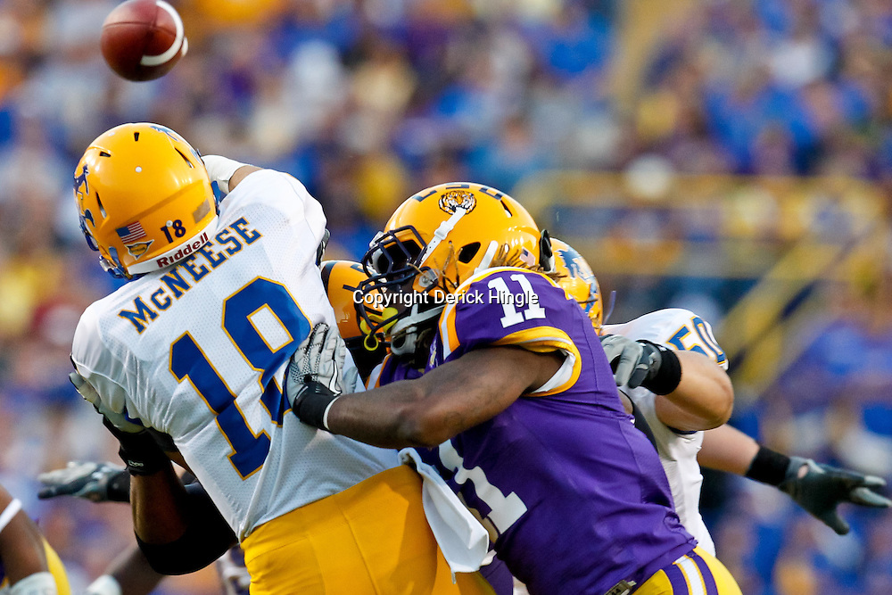 October 16, 2010; Baton Rouge, LA, USA; LSU Tigers linebacker Kelvin Sheppard (11) hits McNeese State Cowboys quarterback Cody Stroud (18) as he throws a pass during the first half at Tiger Stadium.  Mandatory Credit: Derick E. Hingle