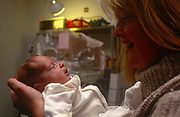 A mother holds her baby staying in intensive care, in the London Hospital, Whitechapel, on 23rd June 1993, in London, England.