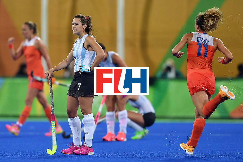 Argentina's Martina Cavallero (2nd L) stands on the pitch as Netherlands' players celebrate after winning the women's quarterfinal field hockey Netherlands vs Argentina match of the Rio 2016 Olympics Games at the Olympic Hockey Centre in Rio de Janeiro on August 15, 2016.  / AFP / MANAN VATSYAYANA        (Photo credit should read MANAN VATSYAYANA/AFP/Getty Images)
