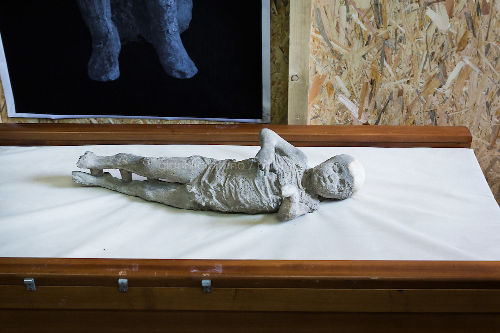 POMPEII, ITALY - 29 SEPTEMBER 2015: The cast of a victim (a child of approximately 4 years old) of the 79 AD Mount Vesuvius eruption is here in a cabin where a CAT scanner has been set up to scan approximately 86 casts that were restored in the archeological site of Pompeii, Italy, on September 29th 2015.<br /> <br /> Pompeii, along with Herculaneum, was buried under 4 to 6 meters (13 to 20 ft) of ash and pumice in the eruption of Mount Vesuvius in 79 AD. After its initial discovery in 1599, Pompeii was rediscovered as the result of intentional excavations in 1748 by the Spanish military engineer Rocque Joaquin de Alcubierre.<br /> <br /> Pompeii is an UNESCO World Heritage Site and one of the most popular tourist attractions of Italy, with approximately 2.5 million visitors every year.