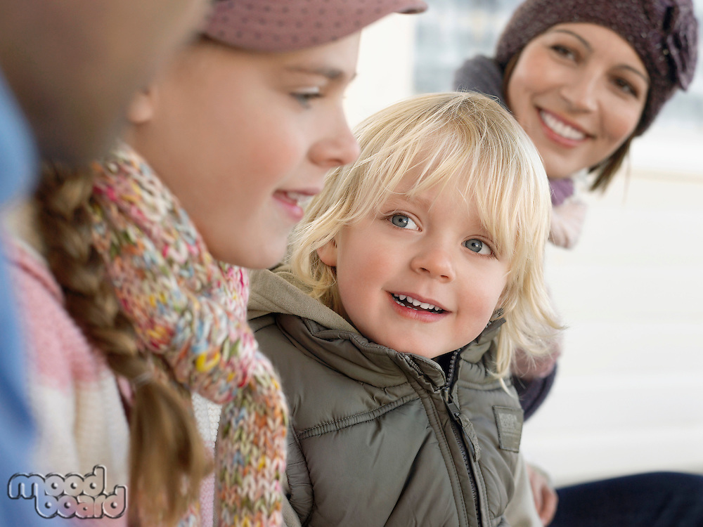 Young boy sitting with family outdoors close up
