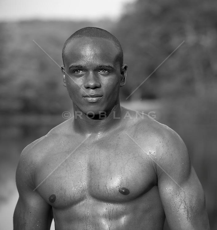 muscular shirtless African American man outdoors