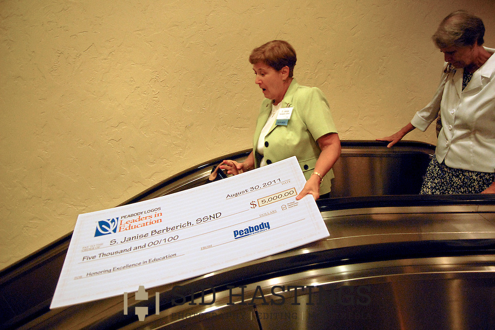 30 AUG. 2011 -- ST. LOUIS -- Sister Janise Berberich, SSND (left), tries to balance the symbolic check for $5,000 she received after being named Educator of the Year at the Peabody Logos Leaders in Education Leadership Recognition Dinner at the Hilton St. Louis at the Ballpark in St. Louis Tuesday, Aug. 30, 2011. Sister Berberich teaches Spanish and Religion at Notre Dame High School in south St. Louis county. At right is NDHS president Sister Gail Guelker, SSND. Photo © copyright 2011 Sid Hastings.